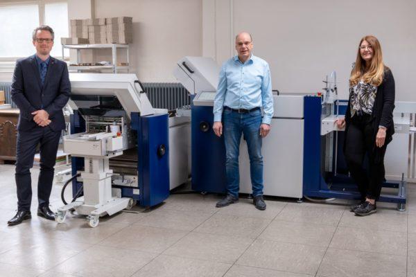 Geschäftsführer Ralf Güllemann (M.) und Assistentin Claudia Klüsener, Güllemann-Druck, sowie Sebastian Scheel, MB Bäuerle, überzeugt die neue Maschine. Foto: MB Bäuerle